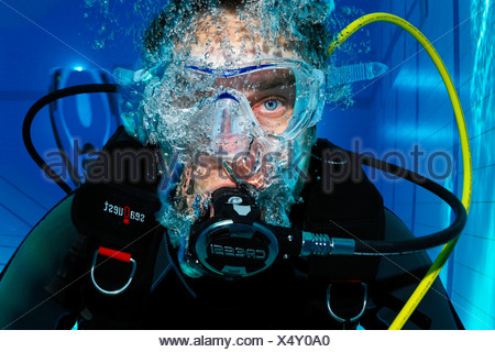 Scuba diver with air bubbles, portrait, in a swimming pool, Nuremberg, Bavaria, Germany - Stock Photo