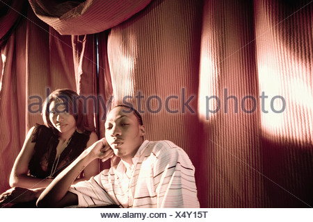 Young couple in hip-hop fashion sitting at a table - Stock Photo
