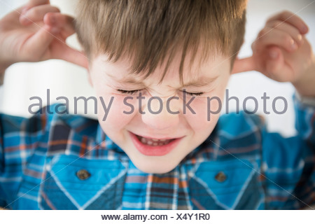 Portrait of boy (4-5) sticking fingers in his ears - Stock Photo
