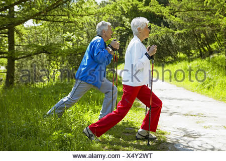 senior couple nordic-walking, warming up - Stock Photo
