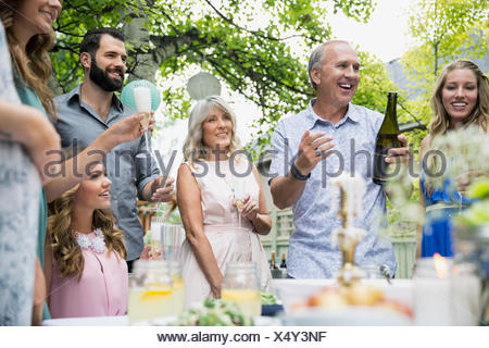 Family drinking celebrating with champagne at garden party - Stock Photo