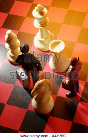 Businessmen figures on a chess board with chess figures - Stock Photo