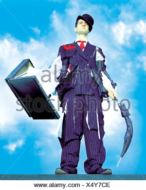 A businessman wearing a tattered suit, holding a briefcase and umbrella - Stock Photo