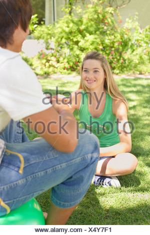 Teenage girl and boy sitting on grass outdoors talking and smiling - Stock Photo