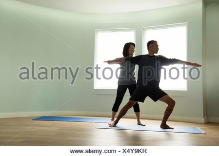 Front view of mature couple doing yoga together, correcting warrior pose - Stock Photo