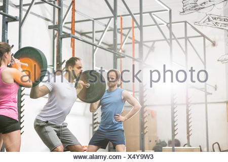 People assisting man in lifting barbell at crossfit gym - Stock Photo