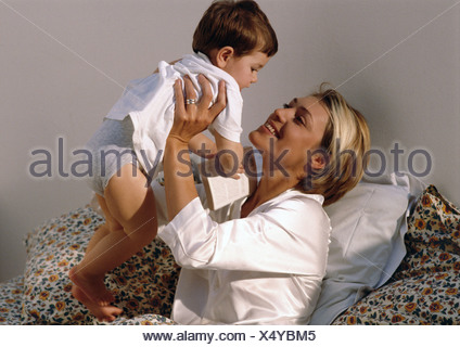 Mother holding up young son in bed. - Stock Photo