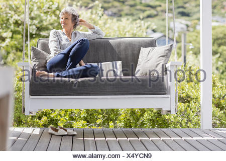 Happy mature woman sitting on a swing in a porch - Stock Photo