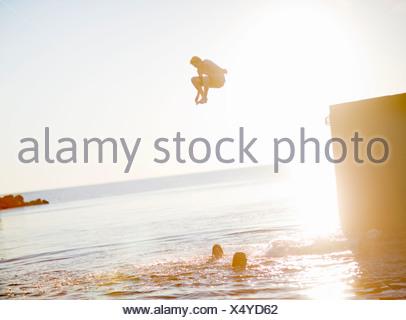 Teenage boy jumping into sea at dusk - Stock Photo