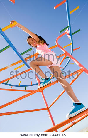 Girl climbing on monkey bars at playground - Stock Photo