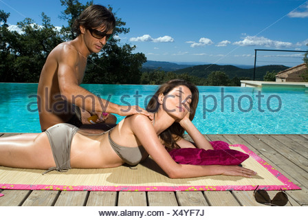 Couple sunbathing by a swimming pool
