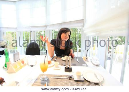 Smiling Mid Adult Woman Sitting While Gesturing At Table - Stock Photo