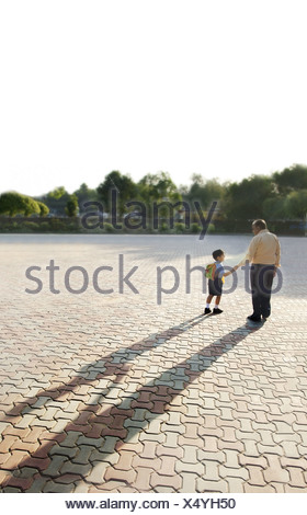 School boy holding his grandfathers hand - Stock Photo