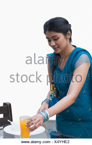 Woman arranging breakfast on a table for her husband - Stock Photo