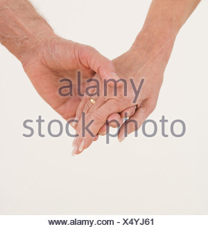 Close up of senior couple holding hands - Stock Photo