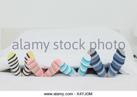 Familys feet in stripey socks at home in bed - Stock Photo