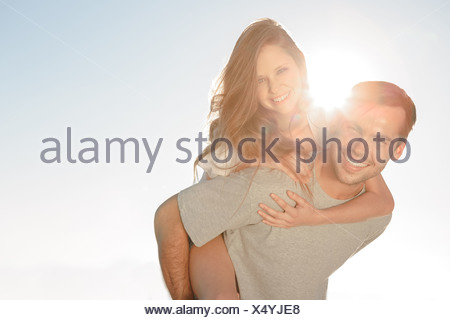 Happy man giving a piggy back to his girlfriend - Stock Photo