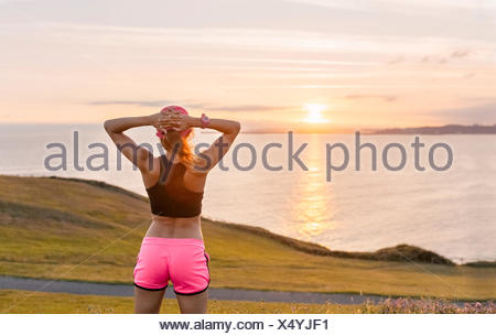 Young woman looking at the sea after workout - Stock Photo