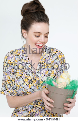 Young woman with easter chick and eggs in flower pot - Stock Photo
