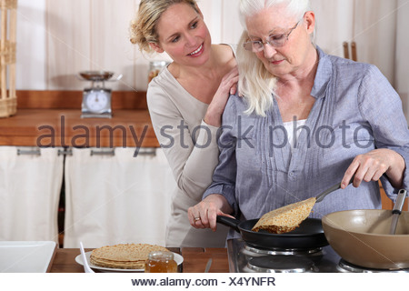 daughter helping her senior mother in the kitchen - Stock Photo