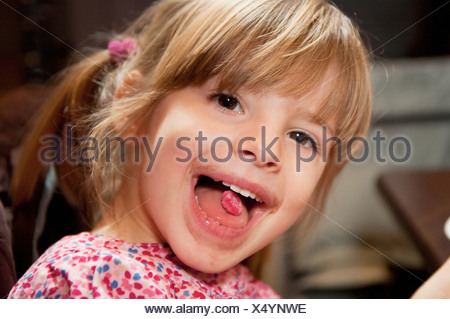 Girl with pink candy on tongue - Stock Photo