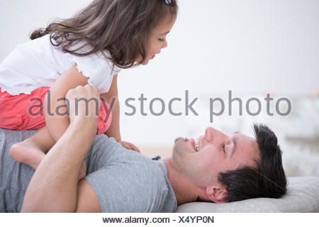 Side view of playful father and daughter at home - Stock Photo