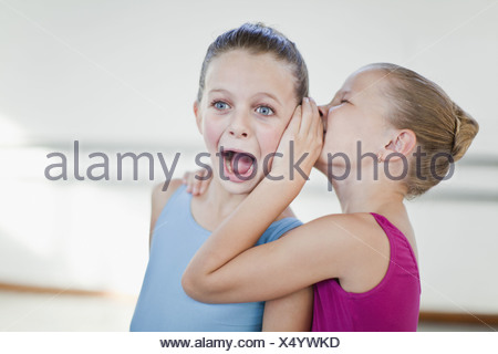 Ballet dancers whispering in studio - Stock Photo