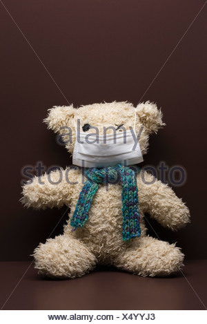 Teddy bear wearing flu mask - Stock Photo
