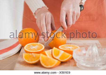 Woman cutting oranges - Stock Photo