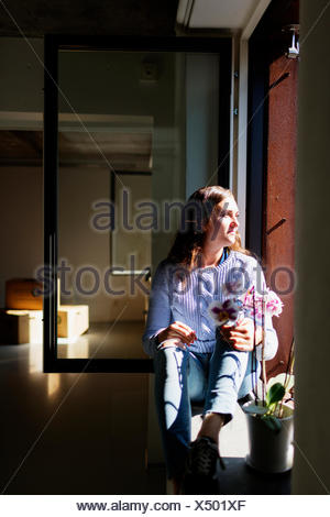 Full length of thoughtful young woman sitting on window sill - Stock Photo