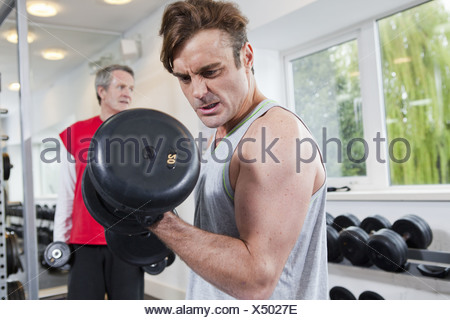 Man lifting weights in gym - Stock Photo