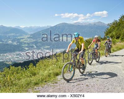 Family on mountain bikes, dirt road, Innsbruck behind, Inn Valley, Tyrol, Austria - Stock Photo