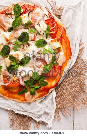 Homemade vegetarian pizza with cottage cheese and tomatoes garnished with mint - Stock Photo