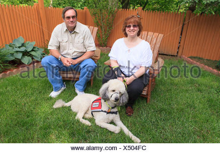 Woman with RSD and her service dog with husband sitting in their back yard - Stock Photo