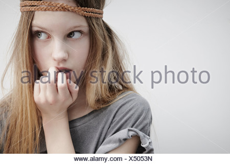 Portrait of girl wearing leather braid around head, holding feather, finger in mouth - Stock Photo