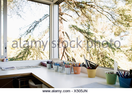 Small office with pots of assorted pens and pencils - Stock Photo
