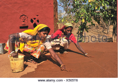 Two women plastering the floor of a courtyard with a mixture of cow dung and sand, Thar Desert, Rajasthan, India, Asia - Stock Photo
