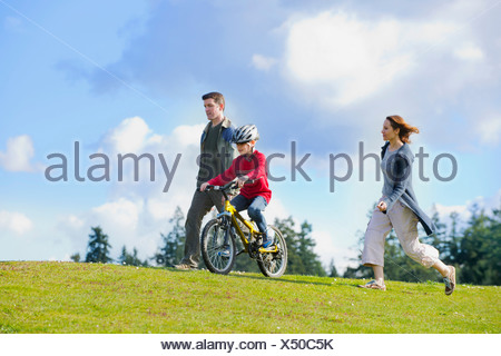 Parents keeping up with son riding bicycle - Stock Photo
