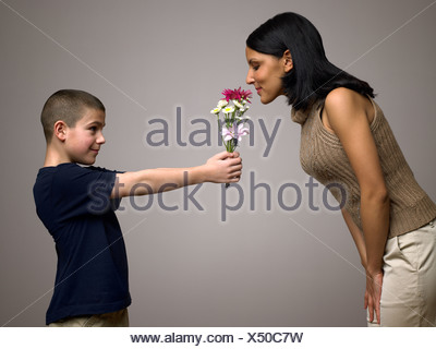 Boy giving flowers to mother - Stock Photo