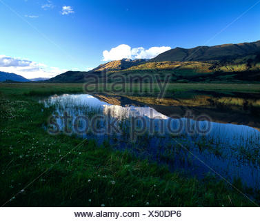 New Zealand. Queenstown Region. Hills reflected in valley lake in late evening shadows. - Stock Photo