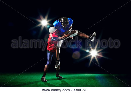 American football players jumping with ball - Stock Photo