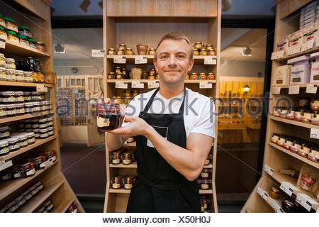 Portrait of mid adult salesman holding jar of jam in grocery store - Stock Photo