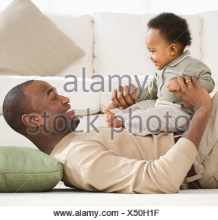 Father playing with baby on floor - Stock Photo