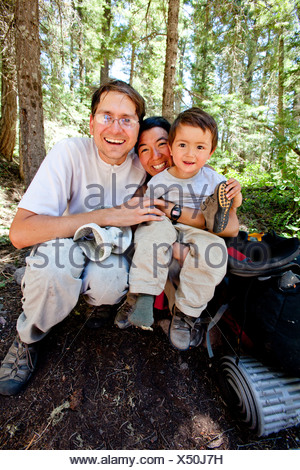 a family sits at the Cimarrona Trail Head for a picture after their 3 night 4 day hiking trip. - Stock Photo