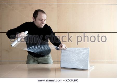 Man wrapping computer with plastic film - Stock Photo