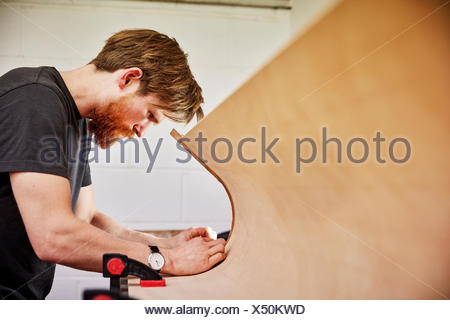 A  man using a tool on the curved cut out edge of a piece of wood - Stock Photo