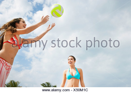 Teenage girls (16-17) playing beach volleyball, low angle view - Stock Photo