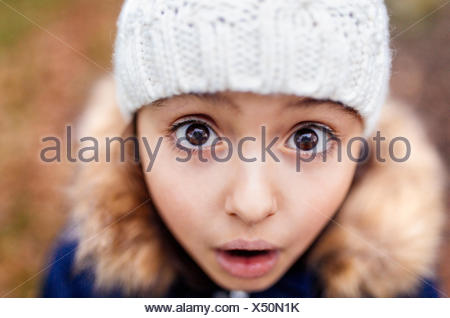 Portrait of little girl with eyes wide open - Stock Photo