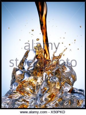 Soda pouring over ice - Stock Photo