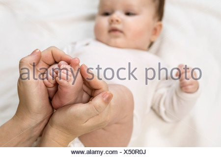 Mother holding child's feet - Stock Photo